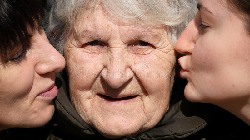 Chica joven y mujer adulta que besan a la abuela en mejillas, abuelita que sonríe y que mira a la cámara Familia tres imágenes de archivo libres de regalías