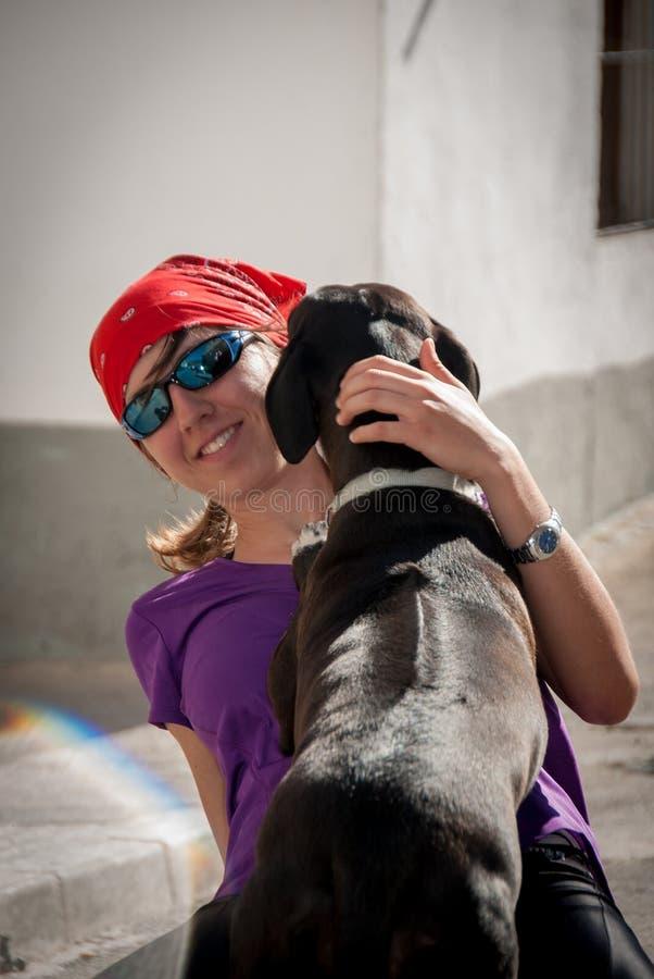 Chica joven y perro negro foto de archivo