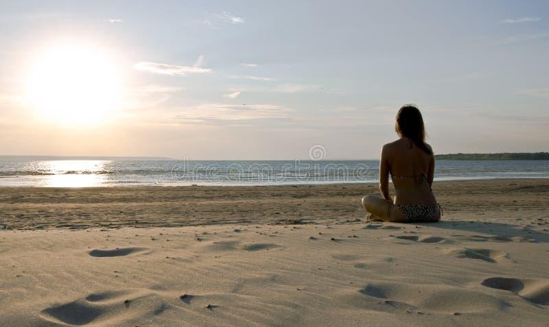 Chica joven y puesta del sol fotos de archivo