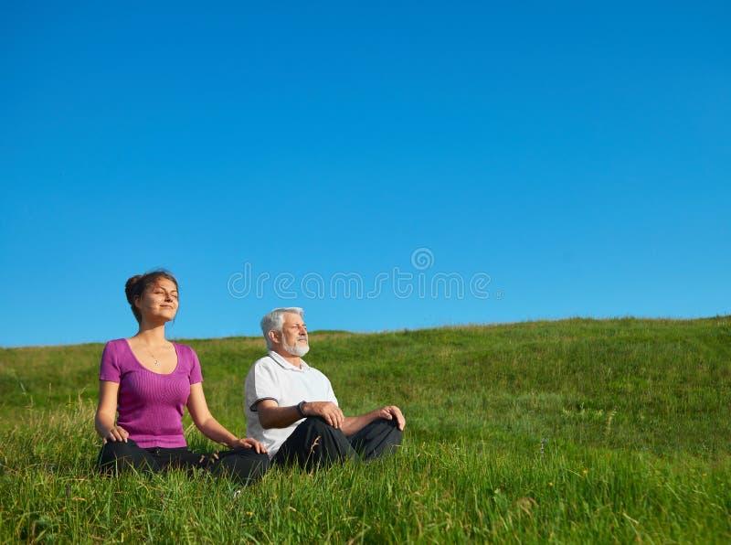 Chica joven y viejo hombre que meditan sentarse en el campo imágenes de archivo libres de regalías