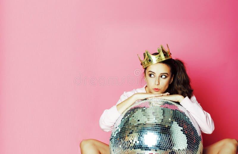 Chica marchosa linda joven como barbie en fondo rosado con la bola de discoteca y la corona imágenes de archivo libres de regalías