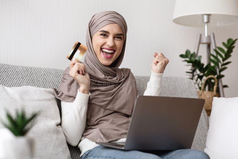 Chica Musulmana Alegre Celebrando El Éxito Con Tarjeta De Crédito Y Portátil imagenes de archivo