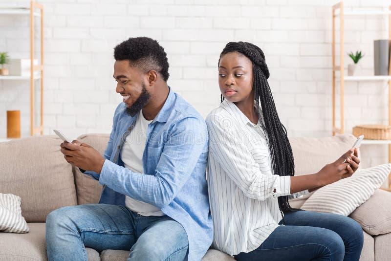Chica Negra Buscando A Shoulder Cómo Su Novio Enviando Mensajes De Texto A Alguien fotos de archivo libres de regalías