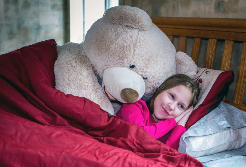 Chica sonriente en la cama con oso de peluche hablante imágenes de archivo libres de regalías