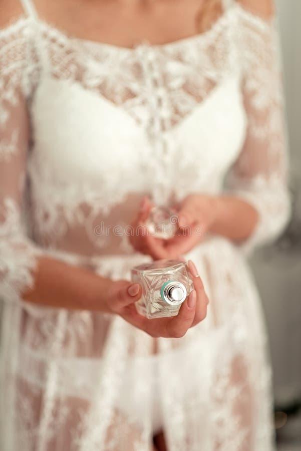 Chica vestida de blanco ofrece perfume imágenes de archivo libres de regalías
