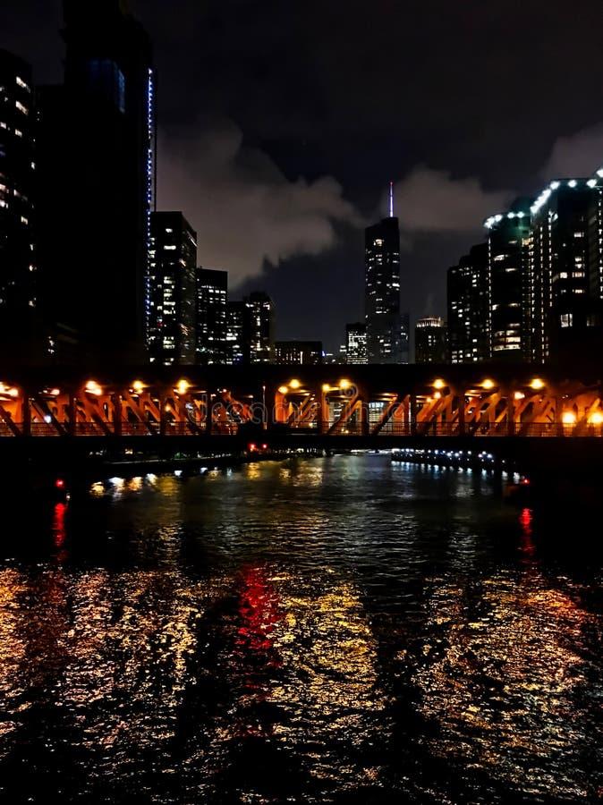 Chicago's市从桥梁和摩天大楼的夜光反射在圈的庄严芝加哥河上 库存照片