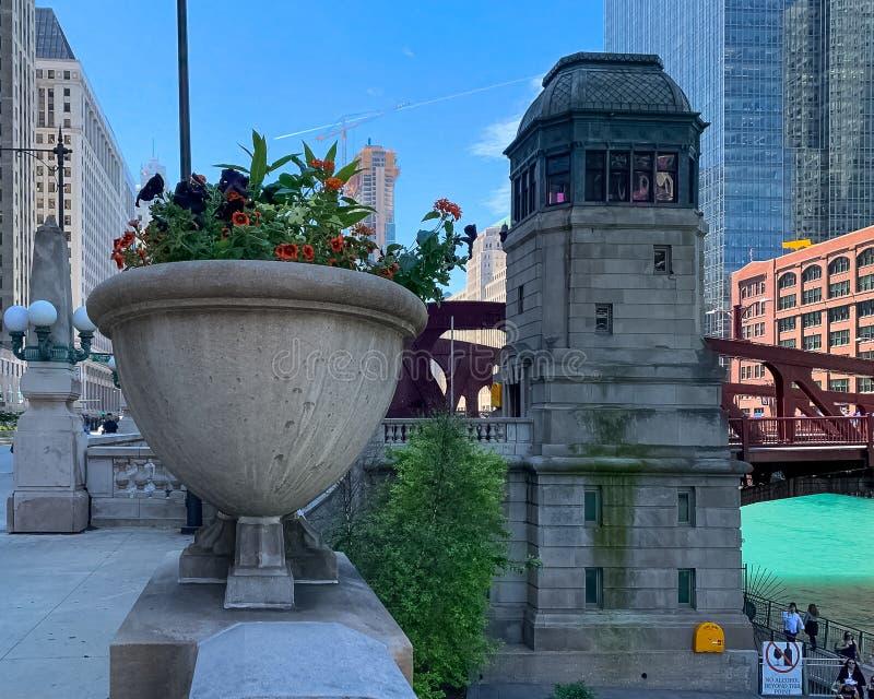 Chicago-Architekturdetail über Wacker Dr. im Sommer, mit Blumenpflanzer auf Bannister im Vordergrund und bridgehouse Schützen stockfotografie