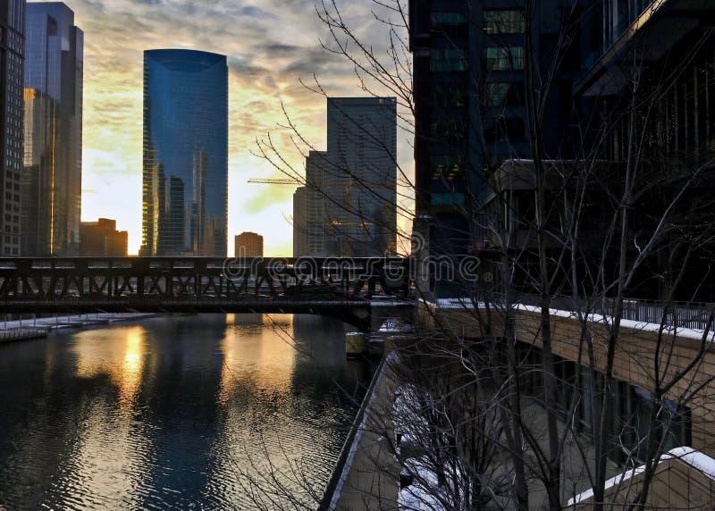 Chicago do centro como a noite ajusta e reflete a arquitetura da cidade em Chicago River durante o inverno foto de stock