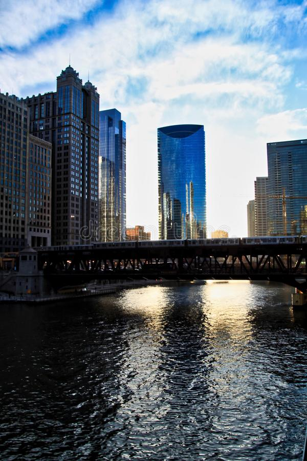 Chicago downtown during sunset and evening commute as an El train passes over Chicago River. royalty free stock image