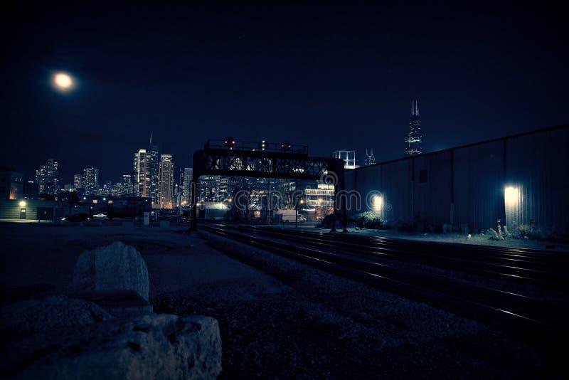 Chicago horisont på natten med drevet spårar att leda in i staden royaltyfri foto