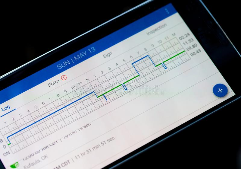Electronic logging device for trucking industry with hours of service displayed on smartphone screen.  stock photos