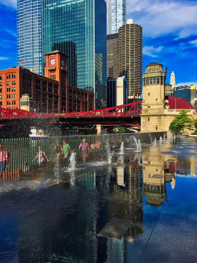 Reflections in the splash pad puddle water of Chicago cityscape. Commuters and tourists walk along the riverwalk in summer. stock photos