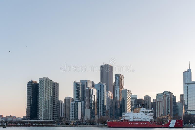 CHICAGO, ILLINOIS - 17 DE ABRIL DE 2016: Arquitetura da cidade de Chicago com arranha-céus e U S Guarda costeira Ship imagem de stock