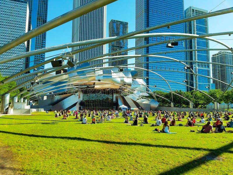 Chicago, Illinois, USA. 07 07 2018. Big group of people practice yoga in Pritzker Pavilion, park Millenium. stock photo