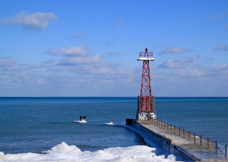 Chicago lighthouse juts out into a frozen Lake Michigan on a freezing winter day in January. Horizon over the great lake with cloudscape hovering stock photos