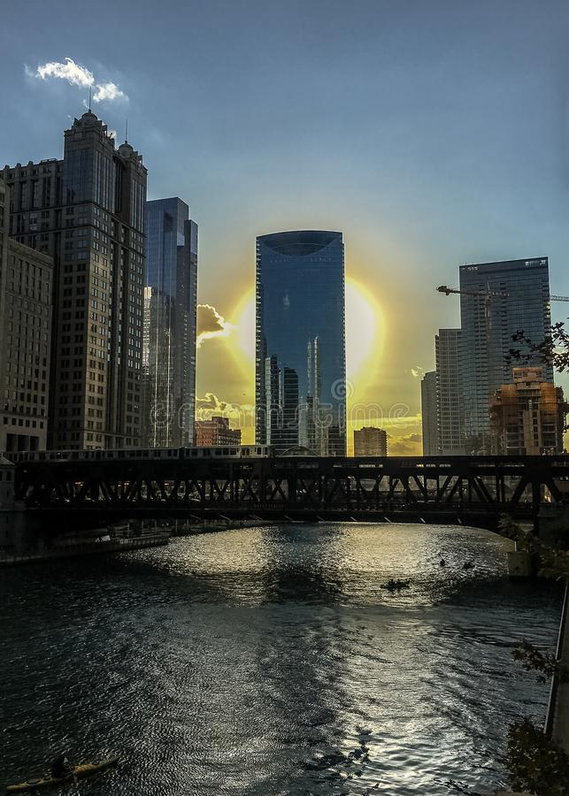 Chicago Loop as the glowing sun sets over the Chicago River as elevated `el` train crosses the water while kayaks float by. stock photos