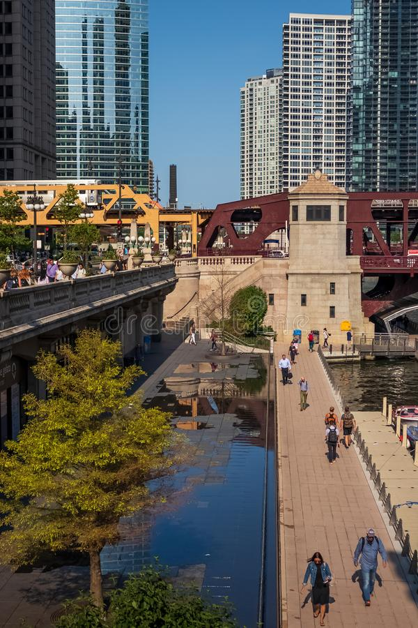 Chicago Loop during rush hour near Chicago River where commuters walk the riverwalk & Wacker Dr. & ride the el train. Chicago, IL / USA - 7/22/19: Chicago Loop stock image