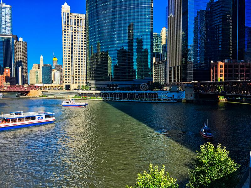 Chicago River during a colorful summer, with tour boats covering the water while tourist and commuter alike utilize the riverwalk royalty free stock photo