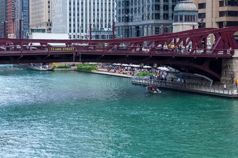 Chicago River during summer as boat crosses under Clark St bridge and people enjoy a riverfront restaurant and winery royalty free stock photography