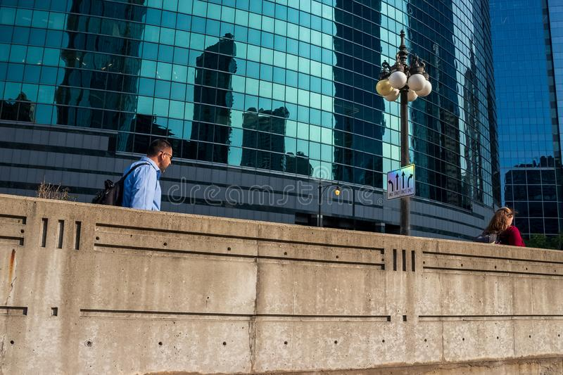 Chicago`s upper Wacker Drive, where pedestrians walk along a wall etched with III, commemorating the 3 forks of the Chicago River stock photos