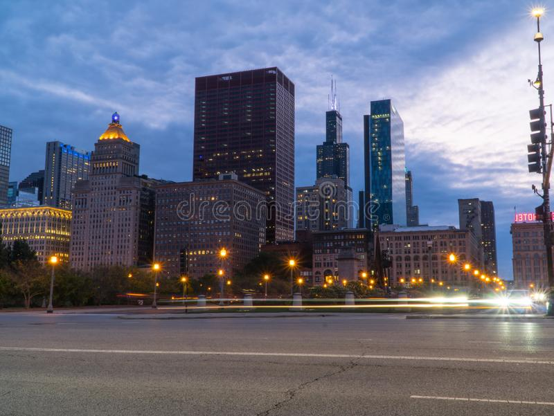 Chicago skyline looking past a busy downtown road. At night with car traffic light trails passing through intersection long exposure stock image