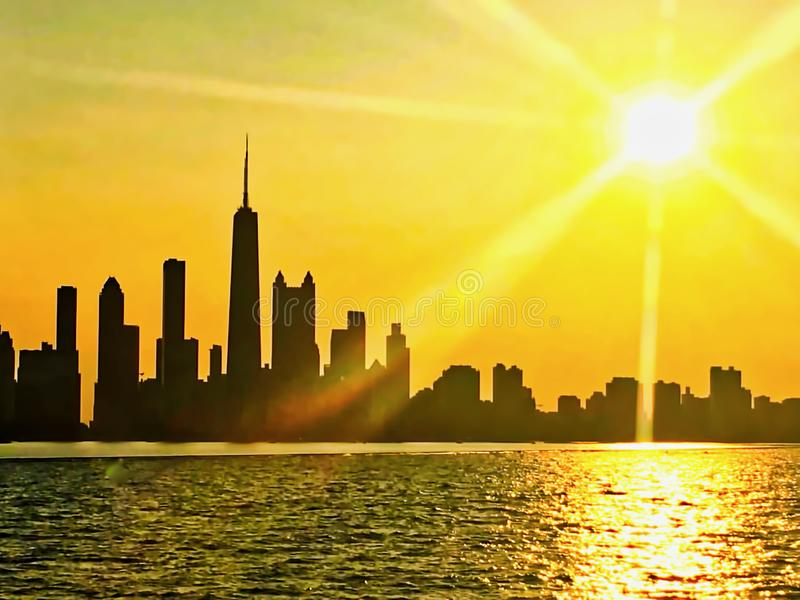 Chicago skyline seen from Lake Michigan, with sunset and sunbeams extending over cityscape during summer royalty free stock photography
