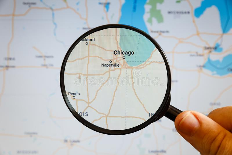 Chicago, United States. Political map. The city on the monitor screen through a magnifying glass in hand royalty free stock image