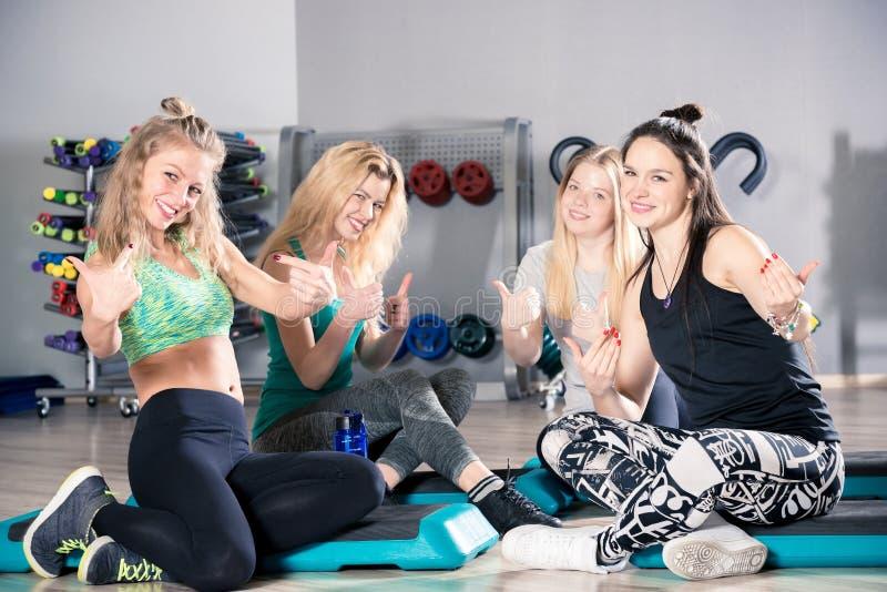 Chicas jóvenes delgadas después de entrenar en la sentada del gimnasio foto de archivo
