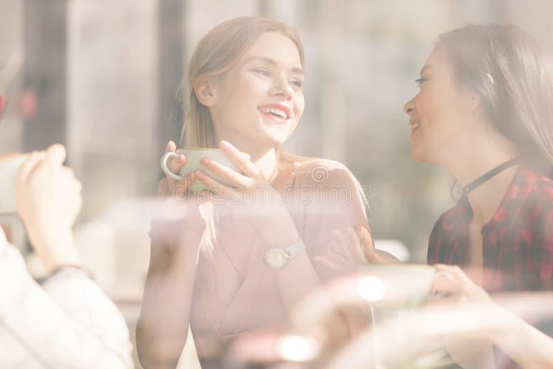 Chicas jóvenes que beben los cócteles juntos mientras que se sienta en la tabla en café imagenes de archivo