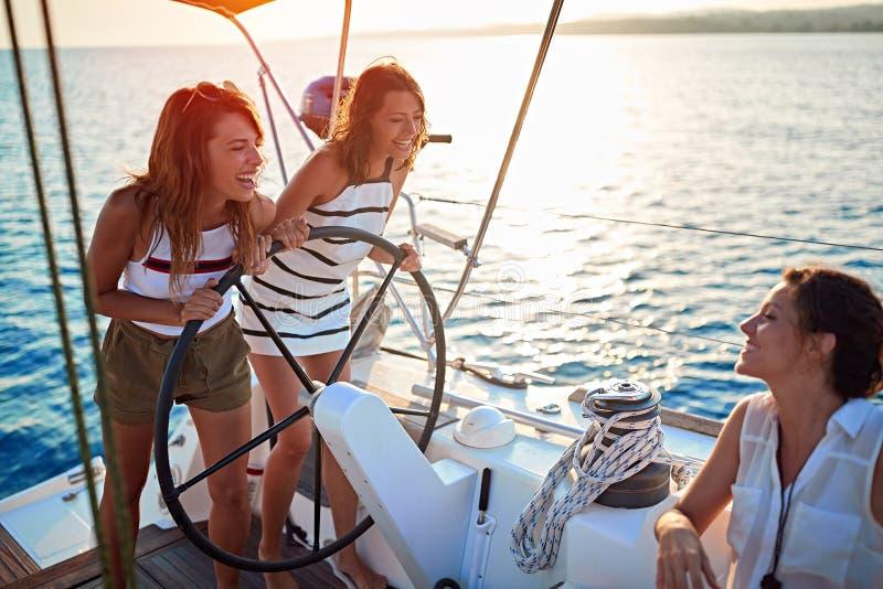 Chicas jóvenes que navegan en el barco junto y gozar en la puesta del sol de vacaciones foto de archivo libre de regalías