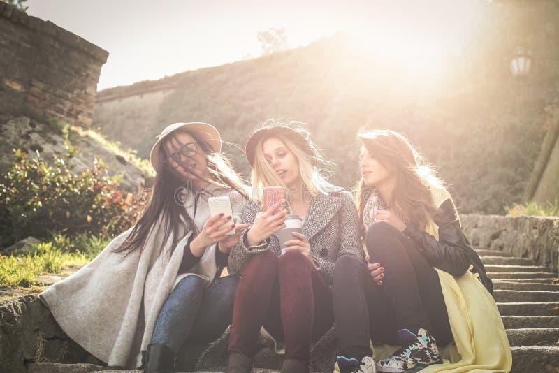 Chicas jóvenes que se sientan en las escaleras en el parque público Thre fotos de archivo libres de regalías