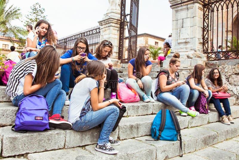 Chicas jóvenes que usan sus teléfonos en Cefalu, Sicilia fotos de archivo