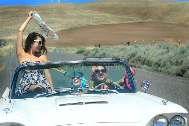 Chicas marchosas felices en convertible foto de archivo