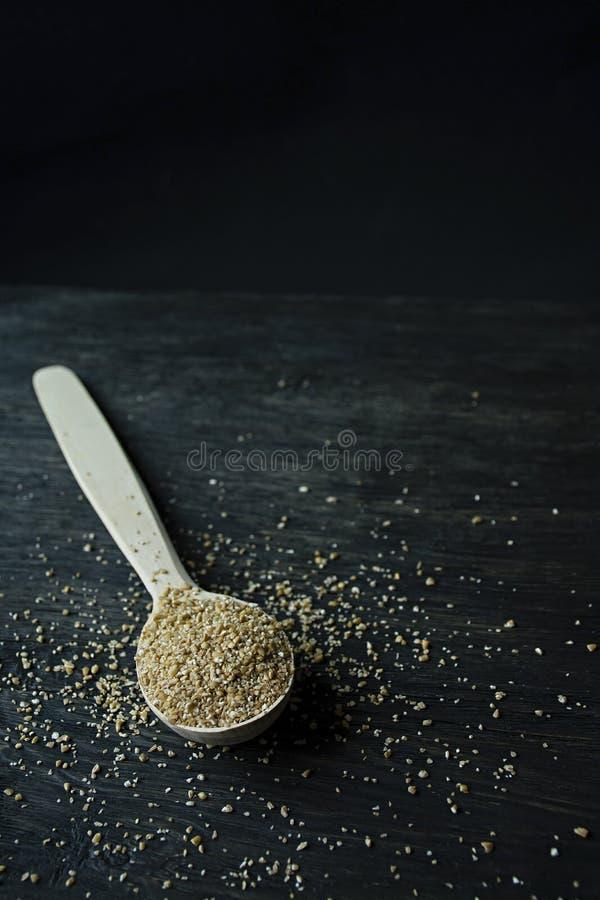 Chicchi del grano in un cucchiaio di legno su un fondo scuro di legno Cucchiaio di legno con i grani del grano fotografia stock