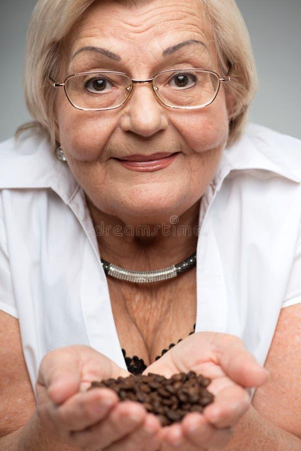Chicchi di caffè anziani della tenuta della donna fotografie stock libere da diritti