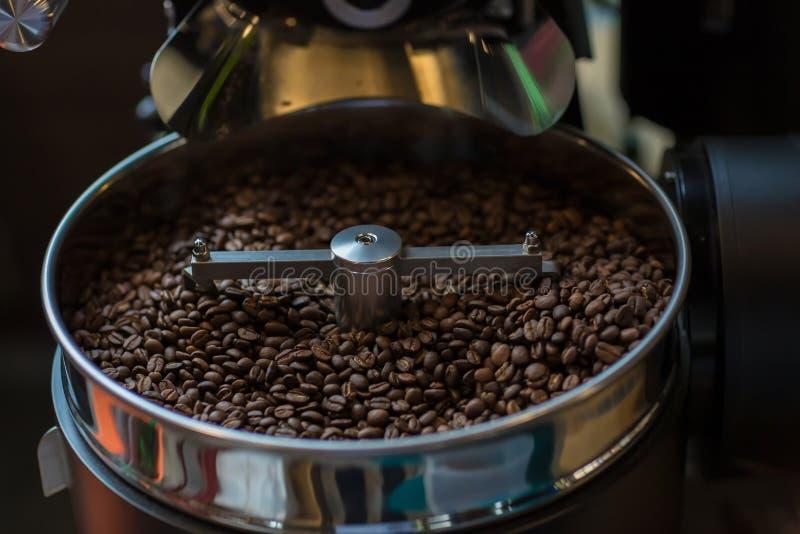 Chicchi di caffè aromatici di recente arrostiti in una macchina moderna di torrefazione Chicchi di caffè freschi - PR di filatura fotografie stock libere da diritti