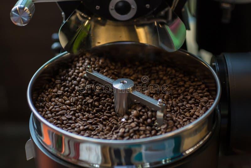 Chicchi di caffè aromatici di recente arrostiti in una macchina moderna di torrefazione Chicchi di caffè freschi - PR di filatura immagine stock libera da diritti