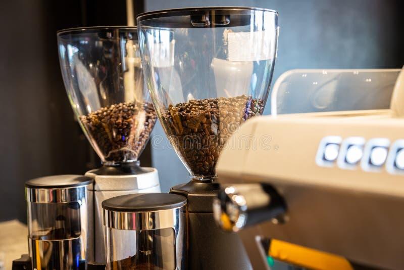 Chicchi di caffè arrostiti in macinacaffè che prepara frantumare caffè, smerigliatrice elettrica di professione nel negozio del c fotografia stock libera da diritti