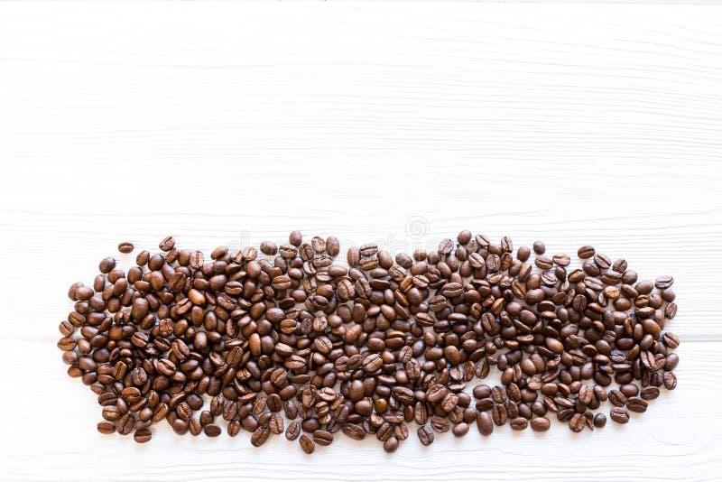 chicchi di caffè arrostiti multipli su fondo di legno strutturale bianco, disposizione piana immagine stock