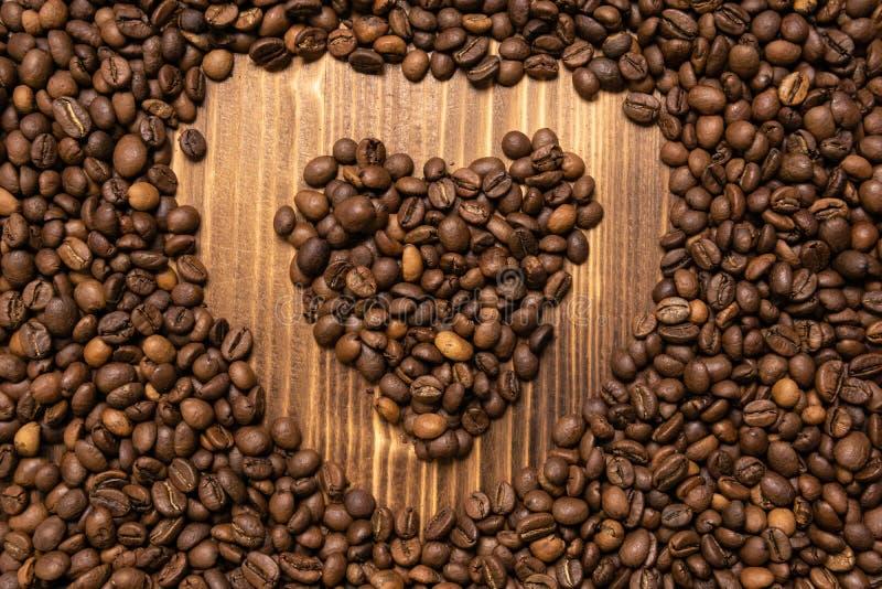 Chicchi di caffè arrostiti sotto forma di fondo di legno del cuore fotografie stock