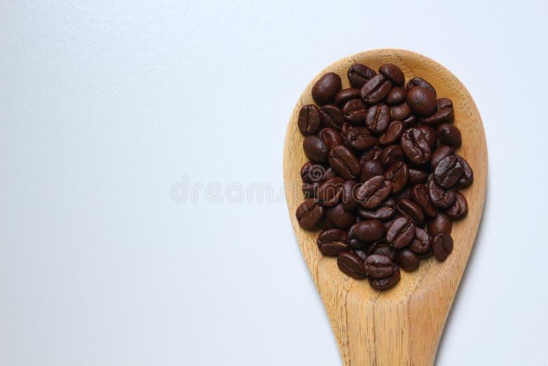 Chicchi di caffè arrostiti sulla siviera di legno immagine stock libera da diritti