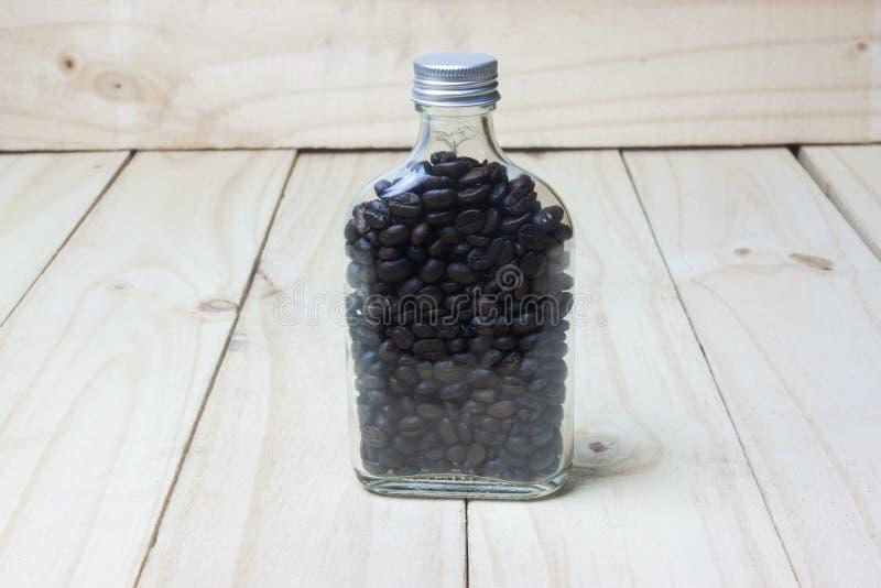 Chicchi di caffè in bottiglia di vetro su fondo di legno fotografie stock libere da diritti
