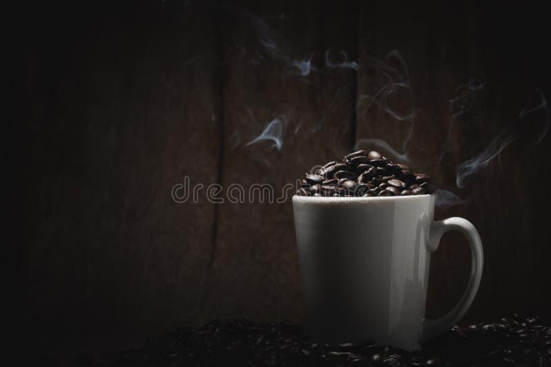 Chicchi di caffè caldi in vetro ed in fumo bianchi sul legno della tavola e immagini stock