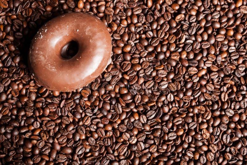 Chicchi di caffè, ciambella e una tazza di caffè fotografie stock libere da diritti