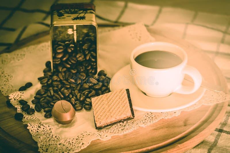 Chicchi di caffè con la tazza bianca con il biscotto fotografie stock