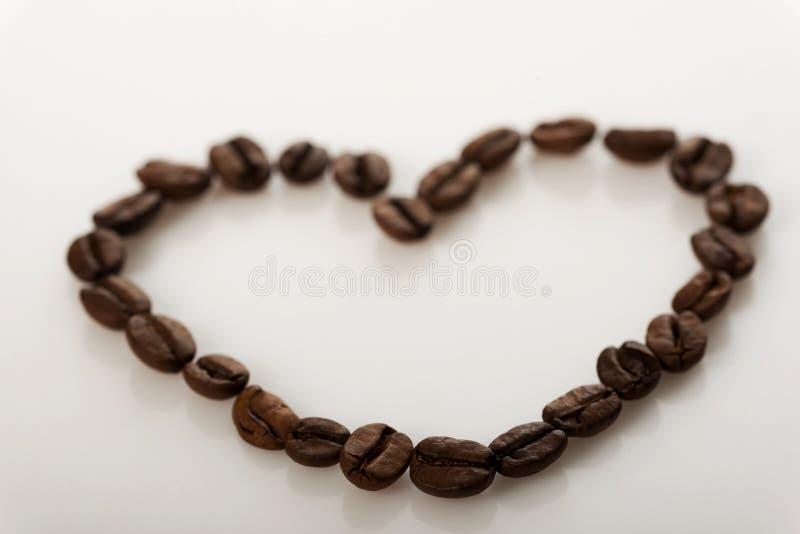 Chicchi di caffè conventionalized a cuore immagini stock libere da diritti