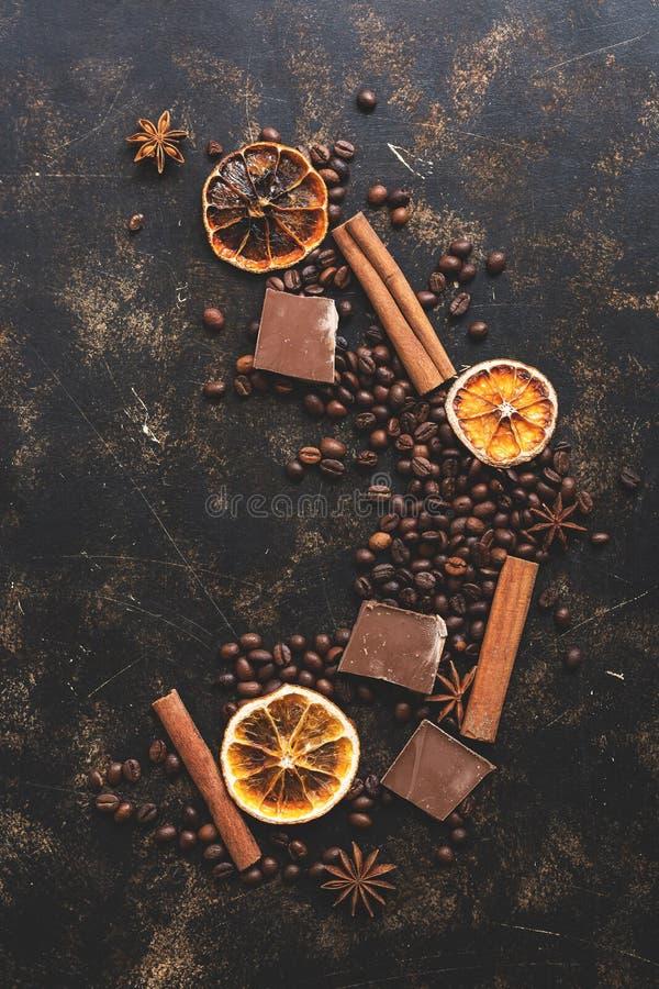 Chicchi di caffè del fondo, bastoni di cannella, anice stellato, fette arancio e cioccolato Fondo rustico di Brown, vista superio fotografia stock