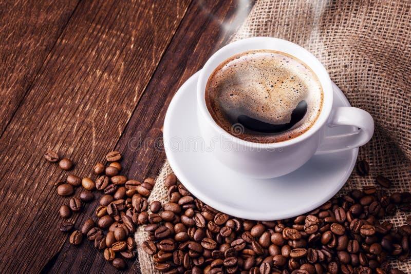 Chicchi di caffè della tazza di legno immagine stock