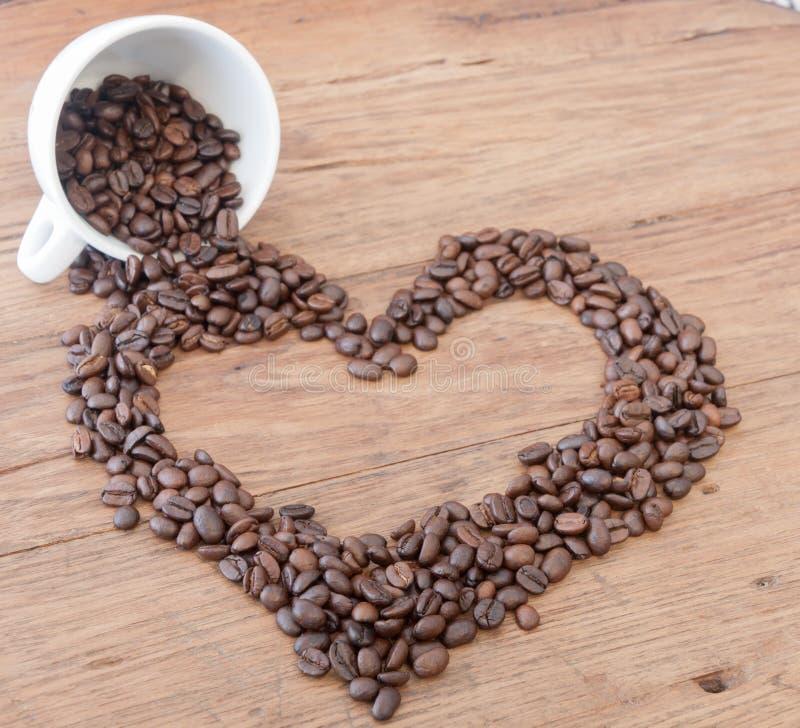 Chicchi di caffè di forma del cuore sulla tavola di legno fotografie stock libere da diritti