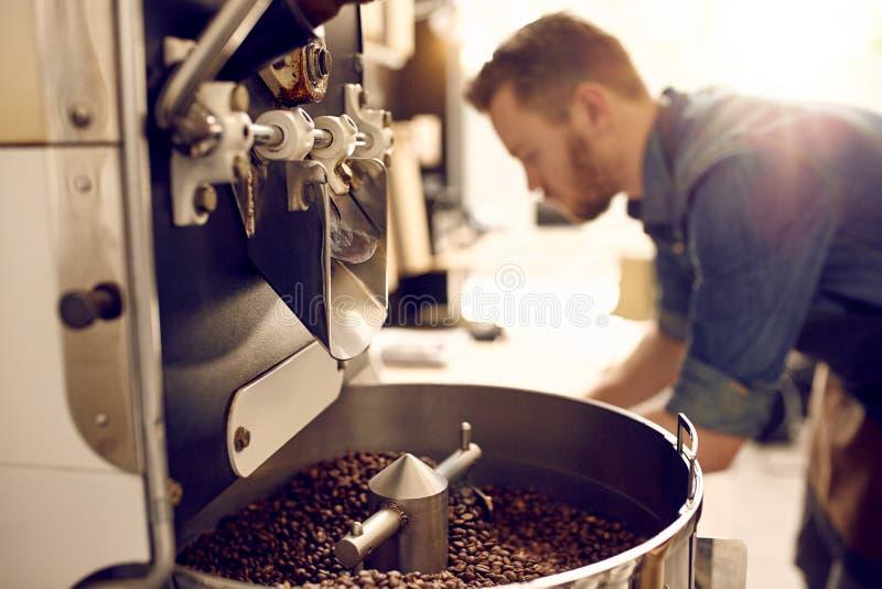 Chicchi di caffè di recente arrostiti in una macchina moderna immagini stock